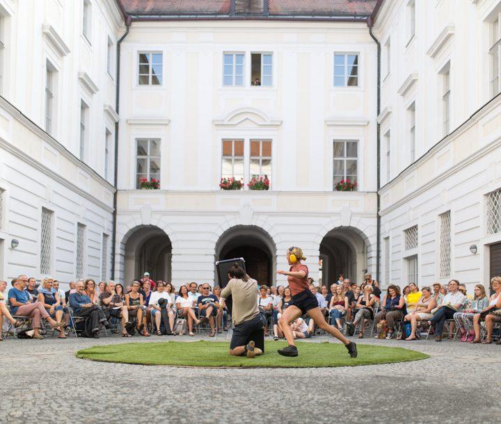 Innenhof mit Straßentheater in der Mitte, Publikum sitzt rundherum