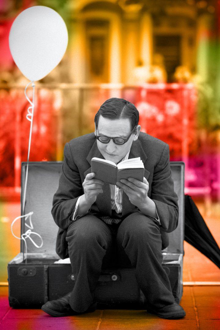 Mann sitzt auf Sessel und liest in einem Buch
