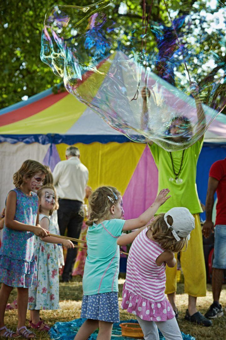 Kinder mit Seifenblasen auf einer Wiese